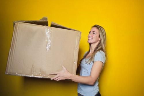 woman-in-grey-shirt-holding-brown-cardboard-box